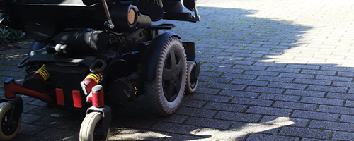 Photo featuring a power wheelchair outside.