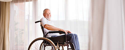 Photo of a man in a wheelchair sitting in front of large windows.