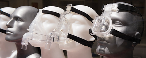 Photo featuring various CPAP masks on mannequin faces.